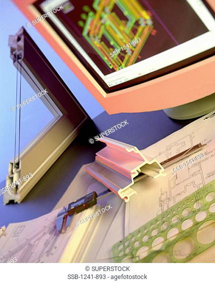 View of vernier caliper and blueprints near a computer monitor