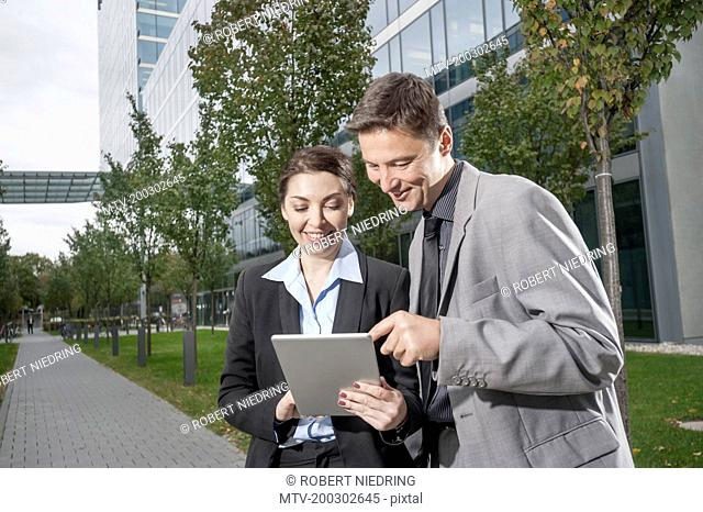 Two business executives working together on a digital tablet, Bavaria, Germany