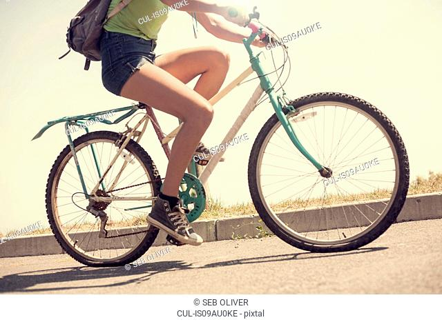Young woman riding bicycle, low section