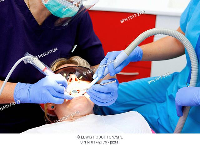 MODEL RELEASED. Patient in dentist's chair with mouth open, dentists using equipment