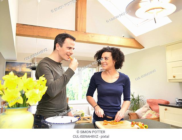 Couple in kitchen tasting and slicing peppers