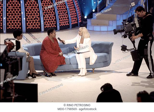 Italian actress and TV host Raffaella Carrà sits on the sofa in the middle of a TV studio, interviewing a black woman and a relative of her