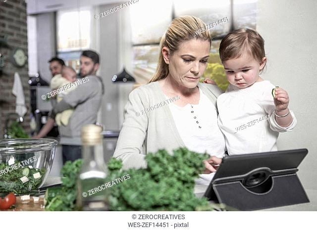 Mother holding baby using tablet in kitchen