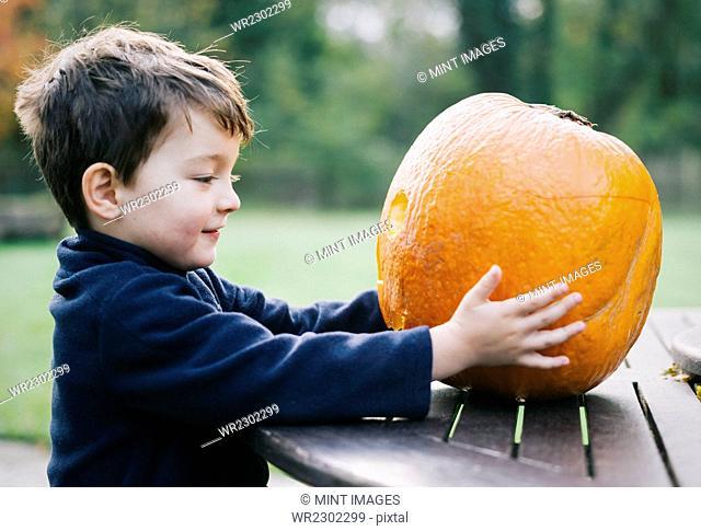 A small boy holding a large orange skinned pumpkin