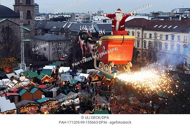 The high-wire artist Falko Traber stands in a sled dressed as Father Christmas above the Christmas market in Karlsruhe, Germany, 05 December 2017