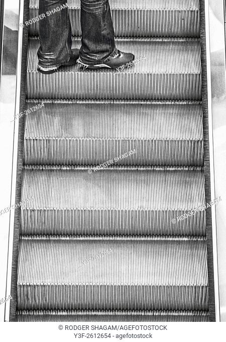 Escalator - black and white. Going up to the next floor - denims covering over legs. Cape Town, South Africa