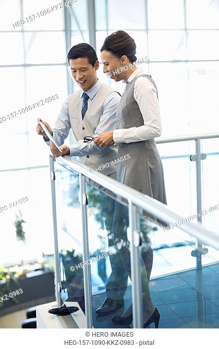 Business people using digital tablet on atrium balcony