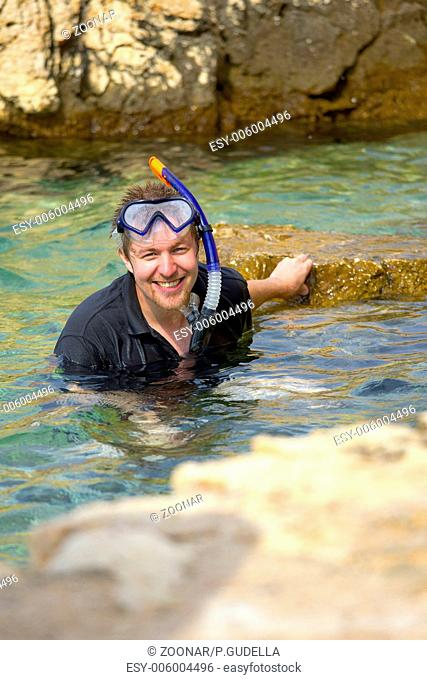 Young man snorkeling happily in the sea