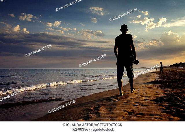 Young man walking by the seaside in summer at dusk