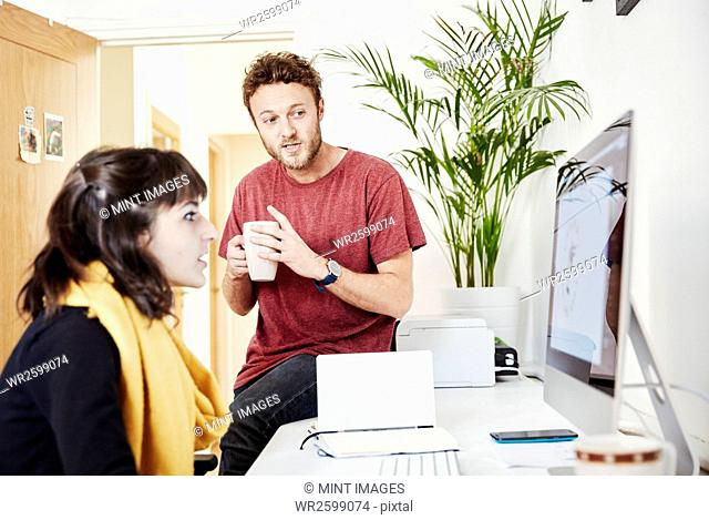 A woman working at a desk and a man sitting on the desk with a coffee cup, talking and looking at the computer screen