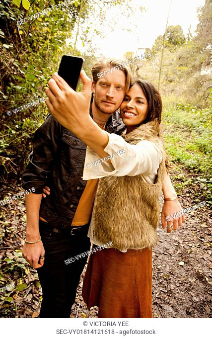 Woman and man taking a selfie in the woods