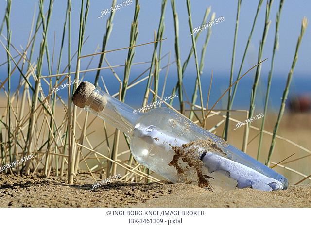 Message in a bottle in sand on a beach, Georgioupolis, Crete, Greece