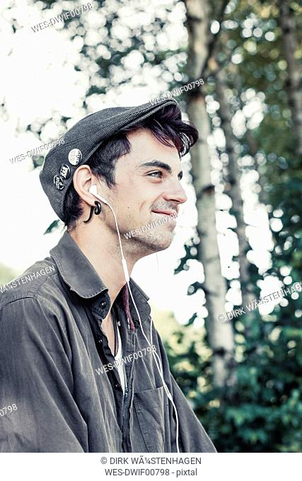 Smiling young man with cap listening music with earphones