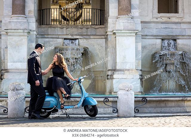 Couple sitting on a vespa scooter. Janiculum water fountain. Rome, Italy