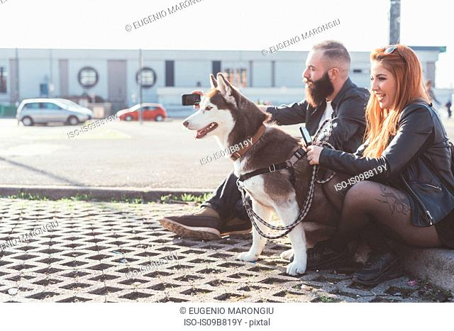Couple sitting with dog looking away