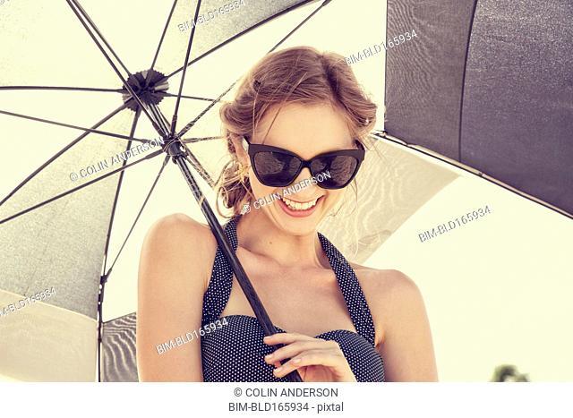 Caucasian woman laughing under parasol