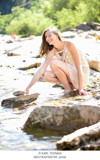 Austria, Villach, young woman relaxing at riverside