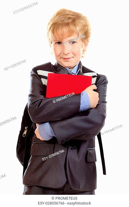 Portrait of a happy schoolboy with backpack and book. Isolated over white background