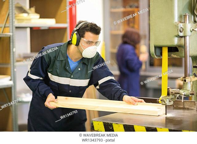 Craftsman wearing safety protection using saw