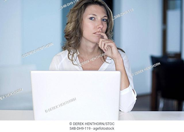 Mid adult woman working on a laptop, thinking
