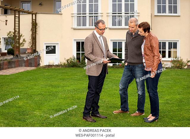 Estate agent presenting potential buyers documents in front of residential house