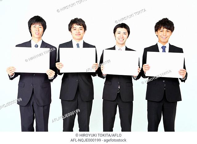 Young Japanese business people holding white boards