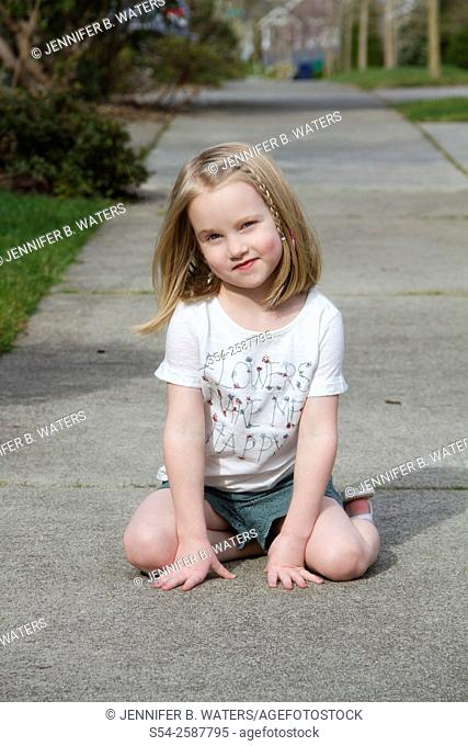 A five-year-old caucasian girl outdoors with a playful expression