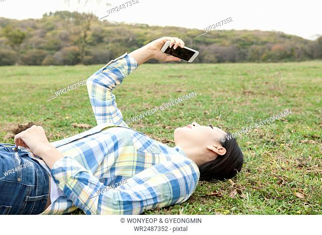 Side view of young woman lying down on grassland holding a smartphone