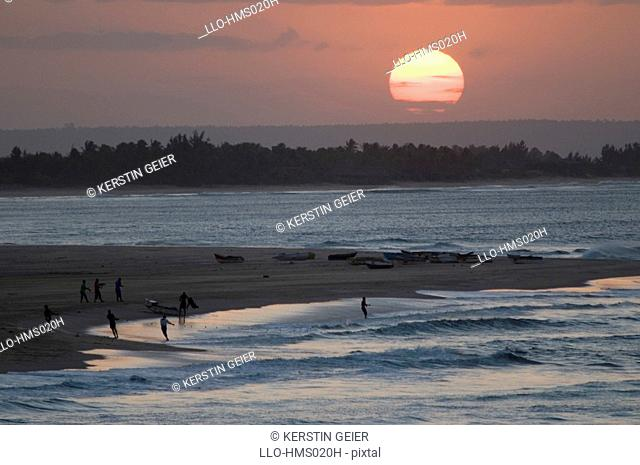 Fishermen pulling in net from shore at sunset, Barra, Inhambane Province, Mozambique
