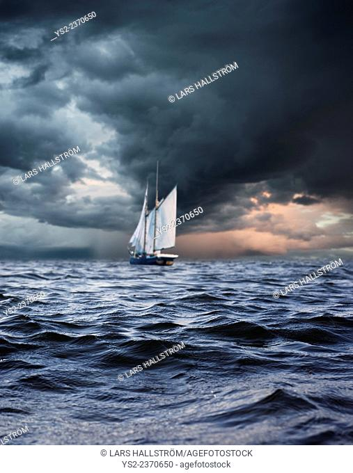 Ship sailing in storm alone at sea. Conceptual image of exploring, solitude and adventure