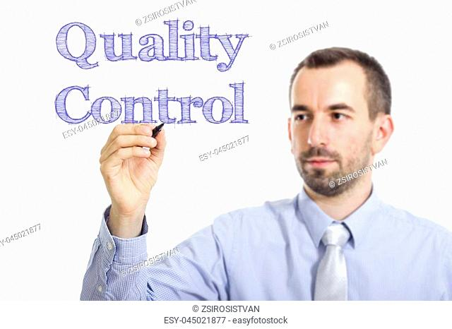 Quality Control - Young businessman writing blue text on transparent surface - horizontal image
