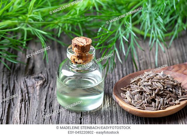 A bottle of essential oil with dill seeds and fresh leaves