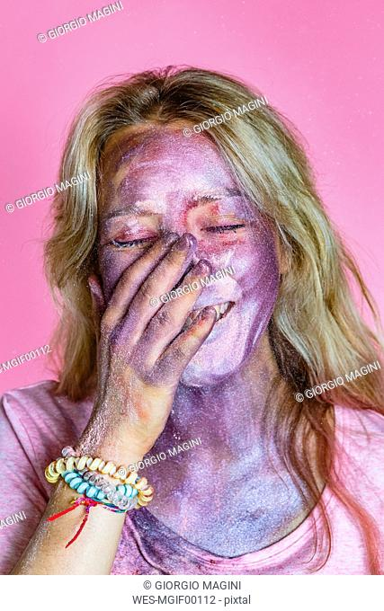 Portrait of laughing young woman with metallic glimmer on her face in front of pink background