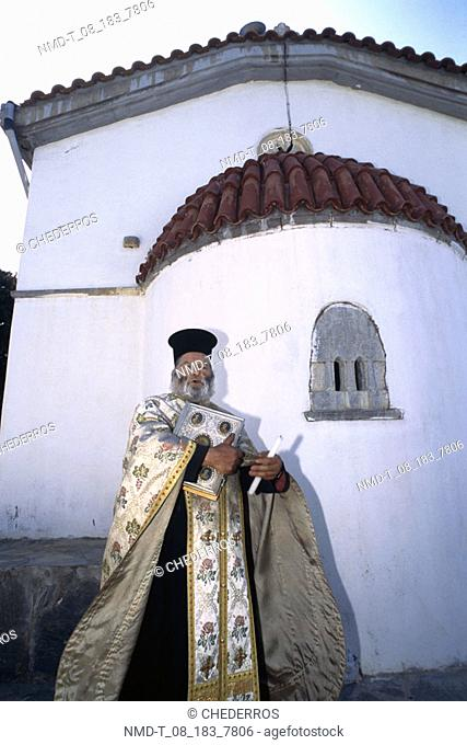 Low angle view of a priest standing in front of a house, Crete, Greece