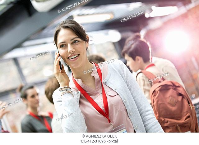 Smiling businesswoman talking on cell phone at conference