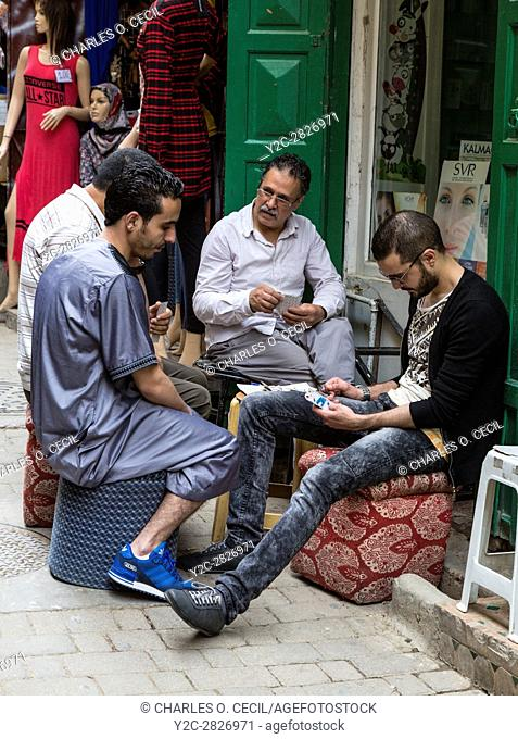 Fes, Morocco. Men Playing Cards on Tala'a Seghira Street in the Medina, Fes El-Bali