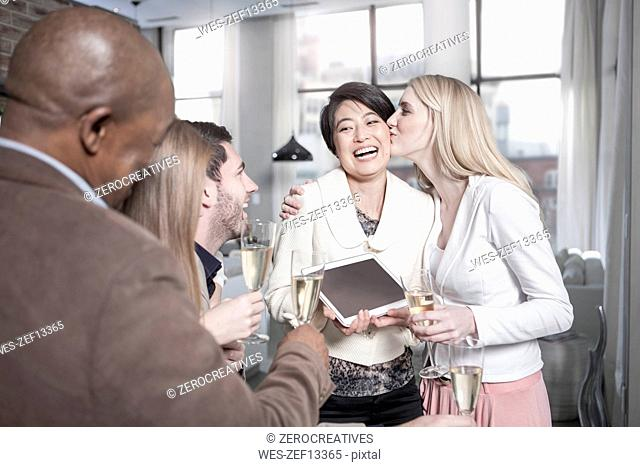 Happy woman showing tablet to friends with champagne glasses at home
