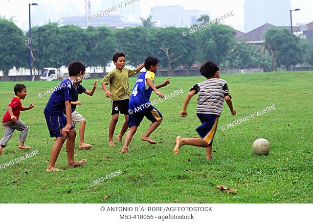 Indonesian children play soccer on a meadown in Kuna Kuningan. Jakarta. Indonesia. Asia