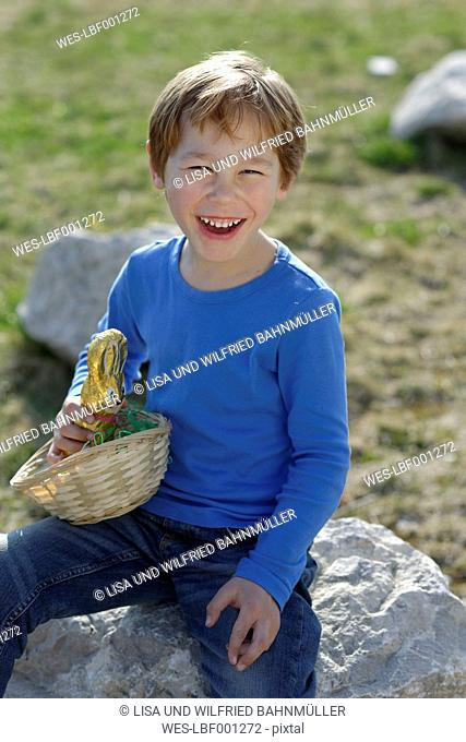 Portrait of laughing little boy with Easter nest and Easter bunny