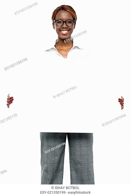 Female business executive holding blank billboard