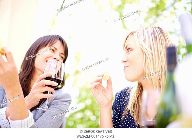 Two happy women with red wine and white bread