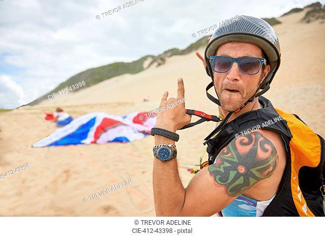 Portrait confident, carefree male paraglider on beach