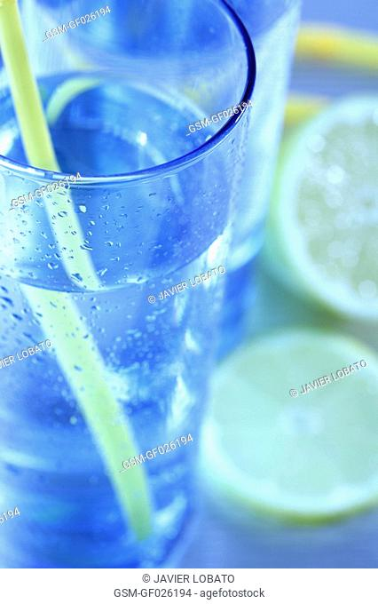 Blue glasses with water, lemons slices and yellow straws detail