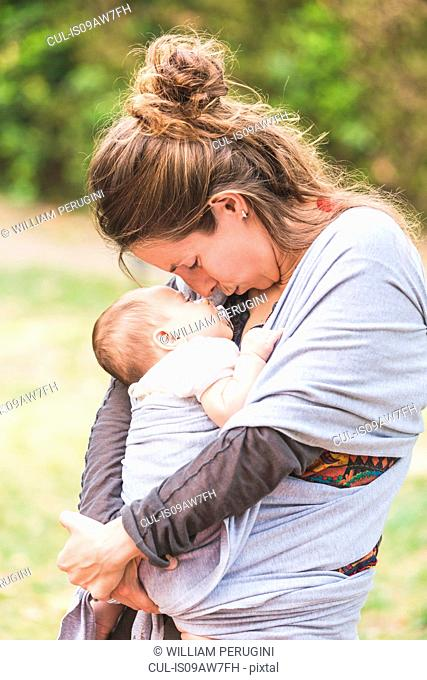 Mother looking down kissing baby girl in baby sling