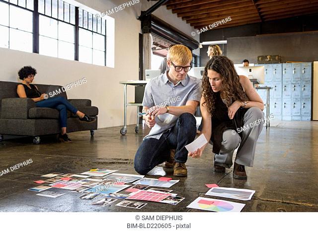 Business people examining paperwork on office floor