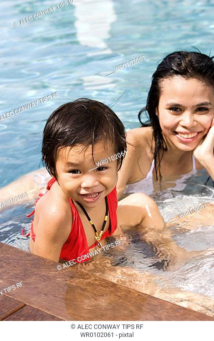 Woman and daughter in swimming pool
