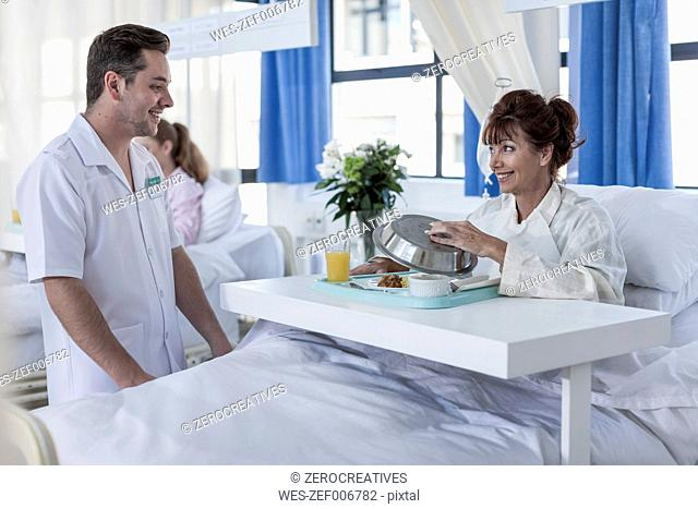 Nurse looking at patient receiving lunch