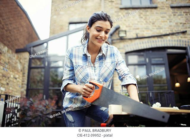 Young woman with saw cutting wood on patio