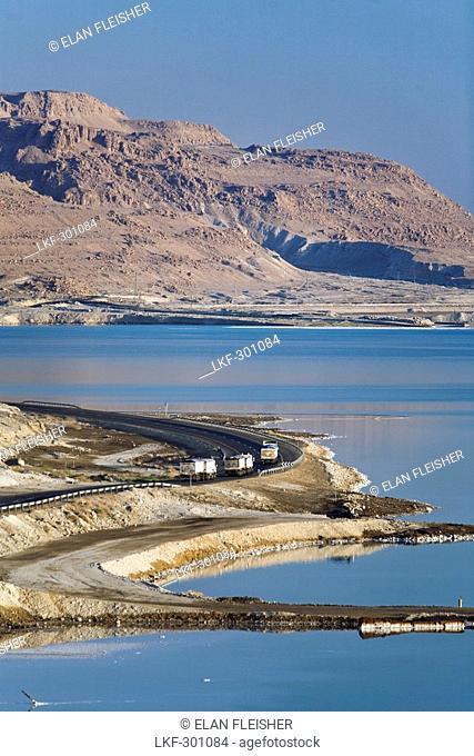 Trucks on road skirting the perimeter of the Dead Sea, En Bokek, Israel, Middle East