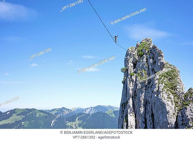 adventurous man balancing on highline slackline in high mountains in Bavarian alps, near mountain Blankenstein, south of Germany